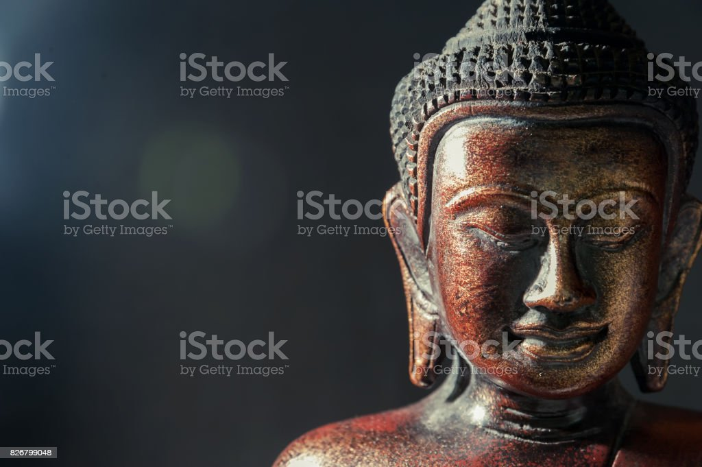 Wooden bronze buddha on black blurred background close up stock photo