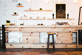 wooden brown bar counter with plants and cupcakes, drawing on shelf in coffee house