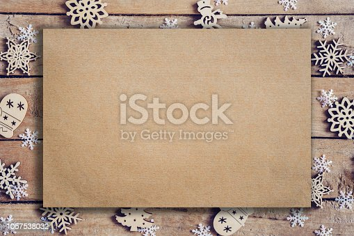 istock Wooden brown christmas background with snowflakes and old brown paper with space. 1057538032