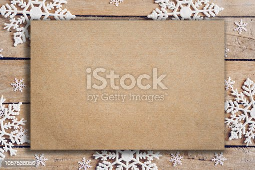 istock Wooden brown christmas background with snowflakes and old brown paper with space. 1057538056