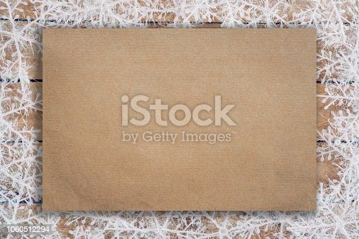 istock Wooden brown christmas background with snowflakes and old brown paper with space. 1060512294