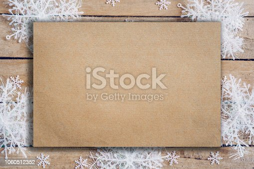 istock Wooden brown christmas background with snowflakes and old brown paper with space. 1060512352