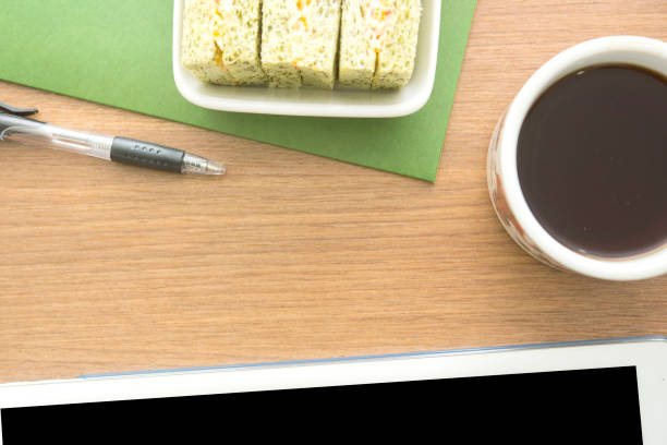 wooden brown office desk with stationary supplies, coffee cup,smart phone,tuna,bread.top view with copy space, flat lay. minimal style - post it notes zdjęcia i obrazy z banku zdjęć