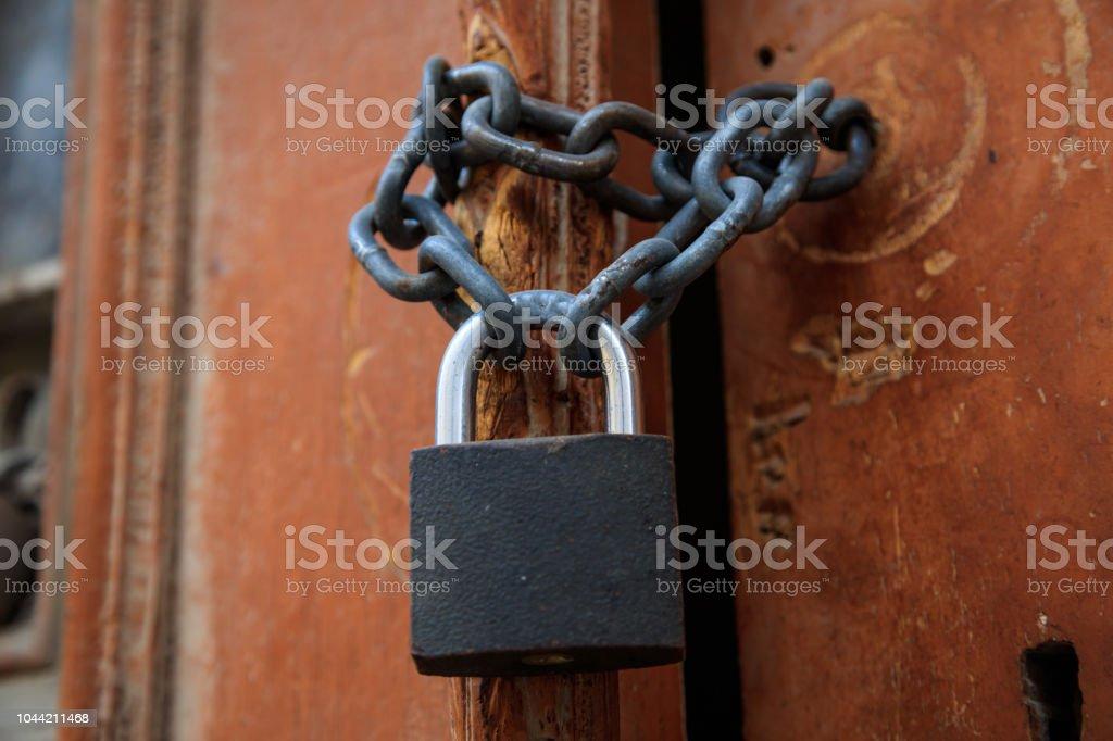 Porta marrom de madeira descascada para segundo plano. Cadeado com corrente proibido a entrada. Close-up, detalhe - foto de acervo