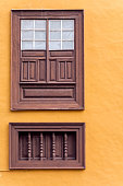 Wooden brown window with shutters. Orange wall.