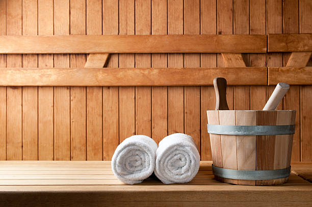 Wooden bucket and white rolled towels in a sauna Detail of bucket and white towels in a sauna. sauna stock pictures, royalty-free photos & images
