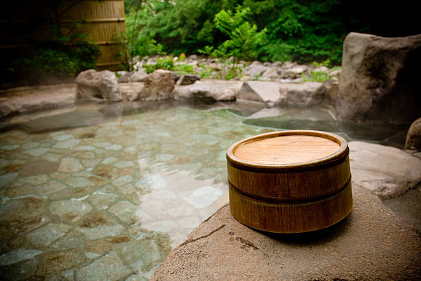 wooden bucket by a japanese hot spring bath - hot spring stock photos and pictures