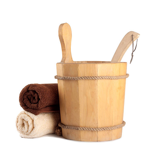 Wooden bucket with ladle for the sauna and stack Wooden bucket with ladle for the sauna and stack of clean towels sauna stock pictures, royalty-free photos & images