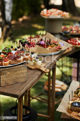 wooden buffet table with snack, appetizer and fruits decorated outdoor in summer day