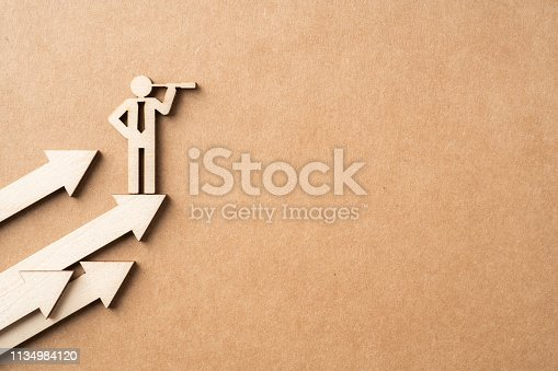 Business and design concept - group of wooden businessman icon with telescope on kraft paper. it's conversation, leadership and teamwork concept