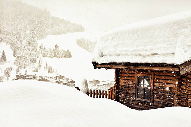 Wooden cabin located in hill covered in white snow stock photo