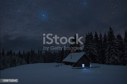 istock Wooden cabin under stars. Lights shines through the window from inside of the house. Night landscape in winter. 1059700342
