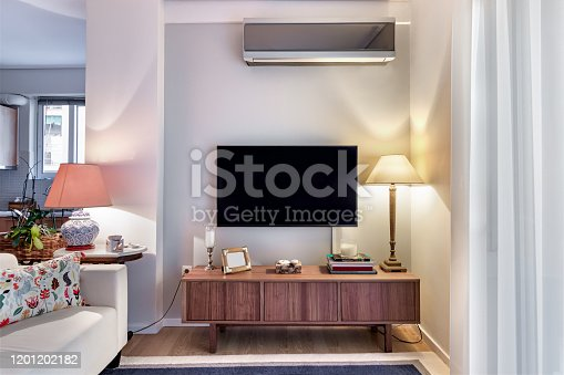 Wooden cabinet with flat tv and Lamps on a very small living room.