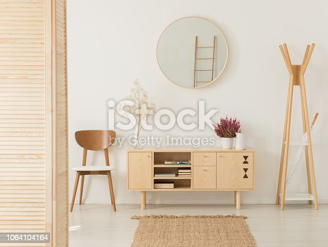 Wooden cabinet with flowers and heather between stylish brown chair and wooden hanger, real photo