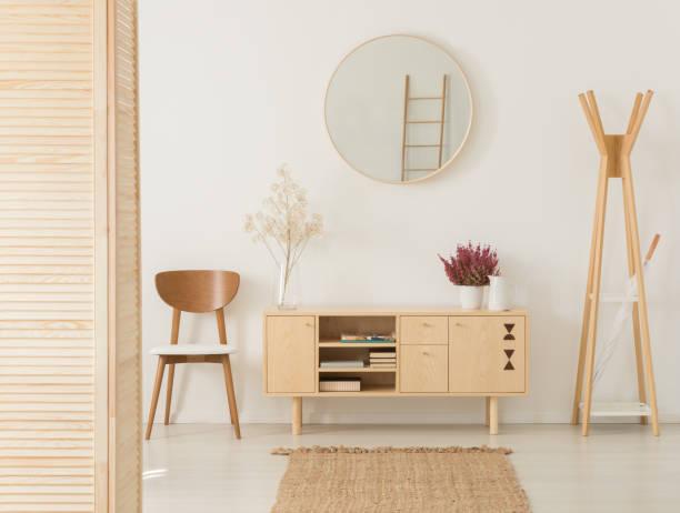 花とスタイリッシュな茶色椅子と木製ハンガー、本物の写真とヘザーの木製キャビネット - 室内装飾 ストックフォトと画像