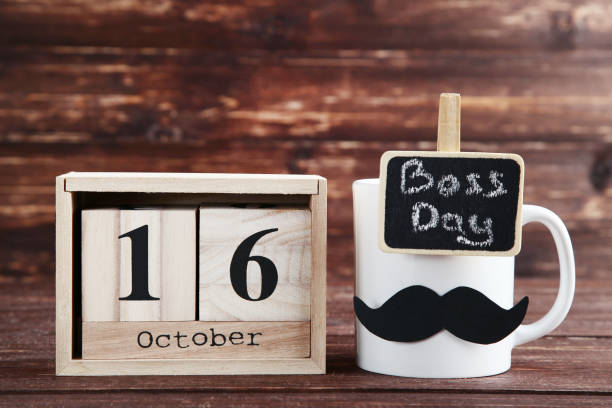 Wooden calendar and white cup with paper mustache. Boss day concept Wooden calendar and white cup with paper mustache. Boss day concept boss's day stock pictures, royalty-free photos & images