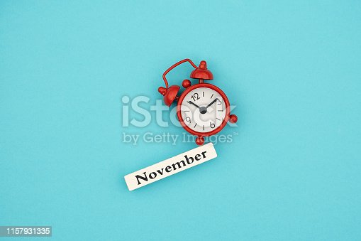 816405814 istock photo Wooden calendar autumn month November and red alarm clock on blue paper background. Concept Hello September. Creative Top view Flat Lay Minimal style 1157931335
