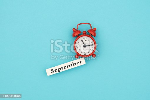 816405814 istock photo Wooden calendar autumn month September and red alarm clock on blue paper background. Concept Hello September. Creative Top view Flat Lay Minimal style 1157931604