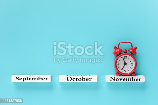 Wooden calendar autumn months and red alarm clock over November on blue background. Concept November time Creative Top view Flat Lay Minimal style Copy space Template