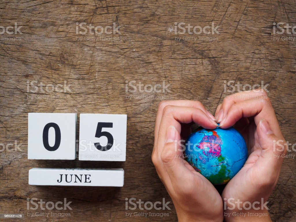 05 JUNE wooden calendar block, globe and stethoscope on wooden texture background top view. World Environment day concept. royalty-free stock photo