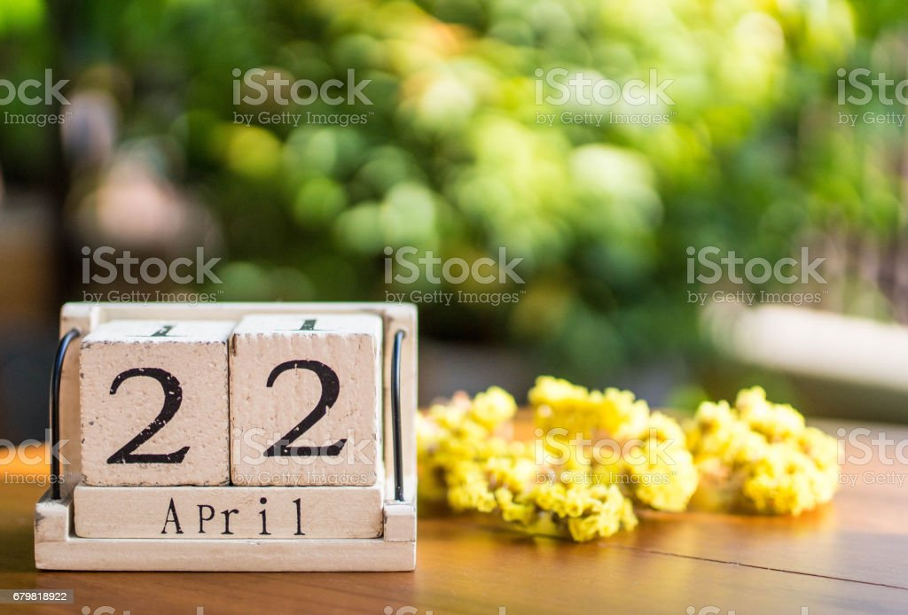 Wooden calendar on wooden desk show the date of April 22 , earth day with nature background stock photo