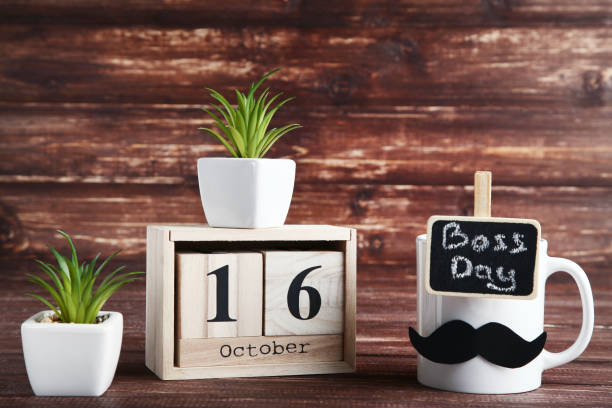 Wooden calendar with green plants and white cup. Boss day concept Wooden calendar with green plants and white cup. Boss day concept boss's day stock pictures, royalty-free photos & images