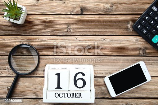 Wooden calendar with magnifying glass and smartphone. Boss day concept