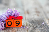 istock Wooden calendar with Russian text May 9 and a bouquet of lilacs on a wooden background. Victory Day. Copy space. 1308558931