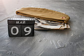 istock Wooden calendar with Russian text May 9 and garrison cap with old photos on a gray background. Victory Day. Copy space. 1305149203
