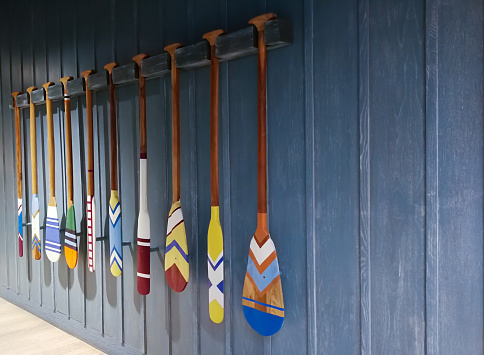 Wooden canoe Boat paddles with different color and shape of blades Hanging on a blue wood background .
