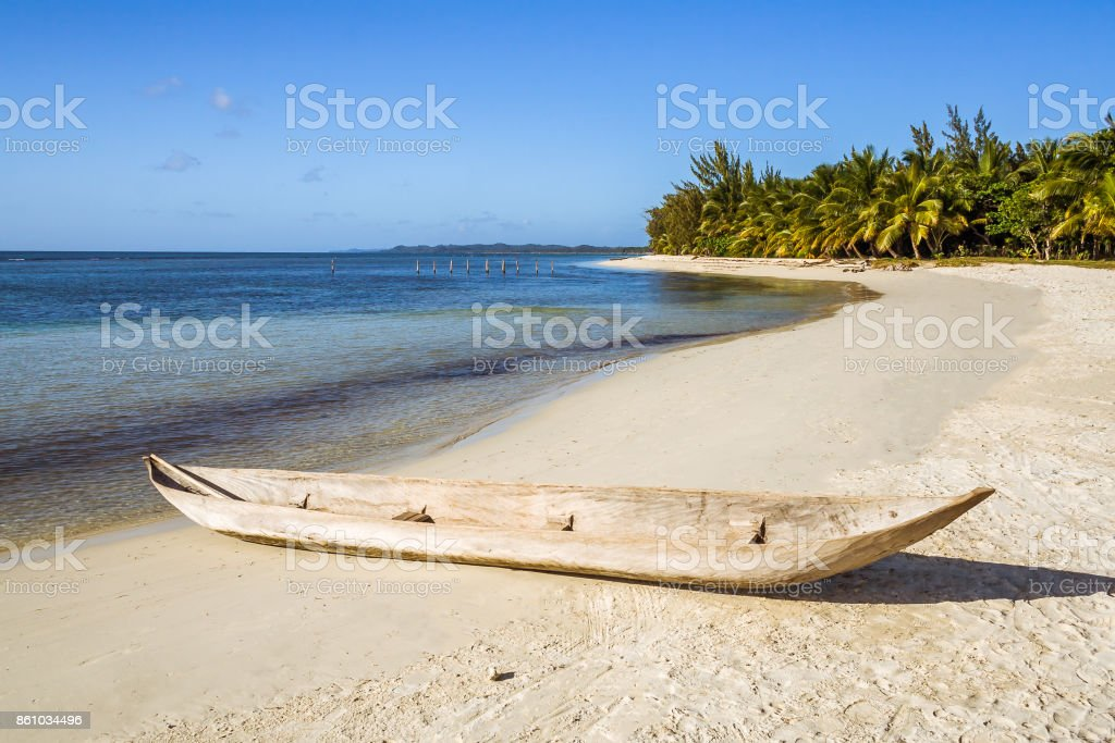 Wooden canoe on the tropical beach stock photo
