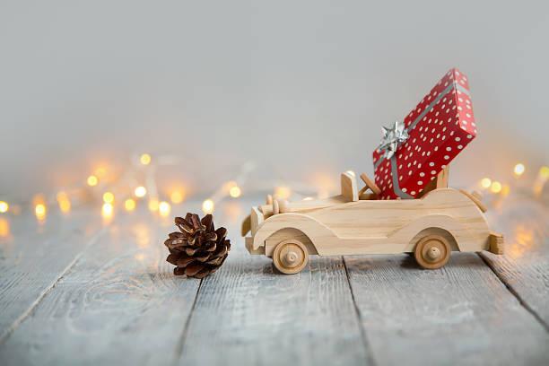 hölzernes auto mit geschenk auf einem hölzernen grauen hintergrund und lichter aus den kranz. weihnachten-konzept - holzspielwaren stock-fotos und bilder