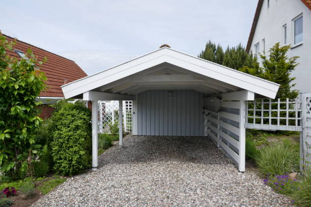 Wooden carport with pitched roof, white with open driveway on pebble floor next to a house. Germany, Europe Carport made of wood next to a house. Semi-open, white with gray back wall, pebble floor pebble floor stock pictures, royalty-free photos & images