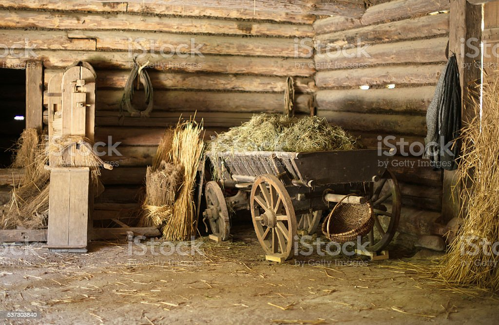 Wooden cart with hay in old barn. stock photo