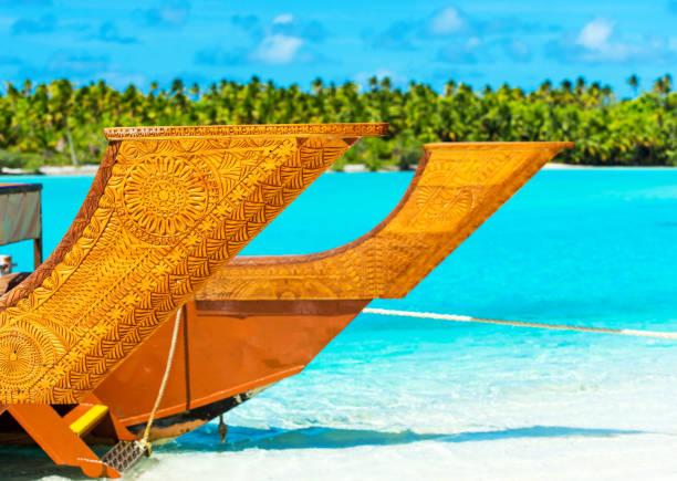 Holzgeschnitztes Boot auf einem Sandstrand auf der Insel Aitutaki, Cook Islands, Südpazifik. Mit selektivem Fokus – Foto