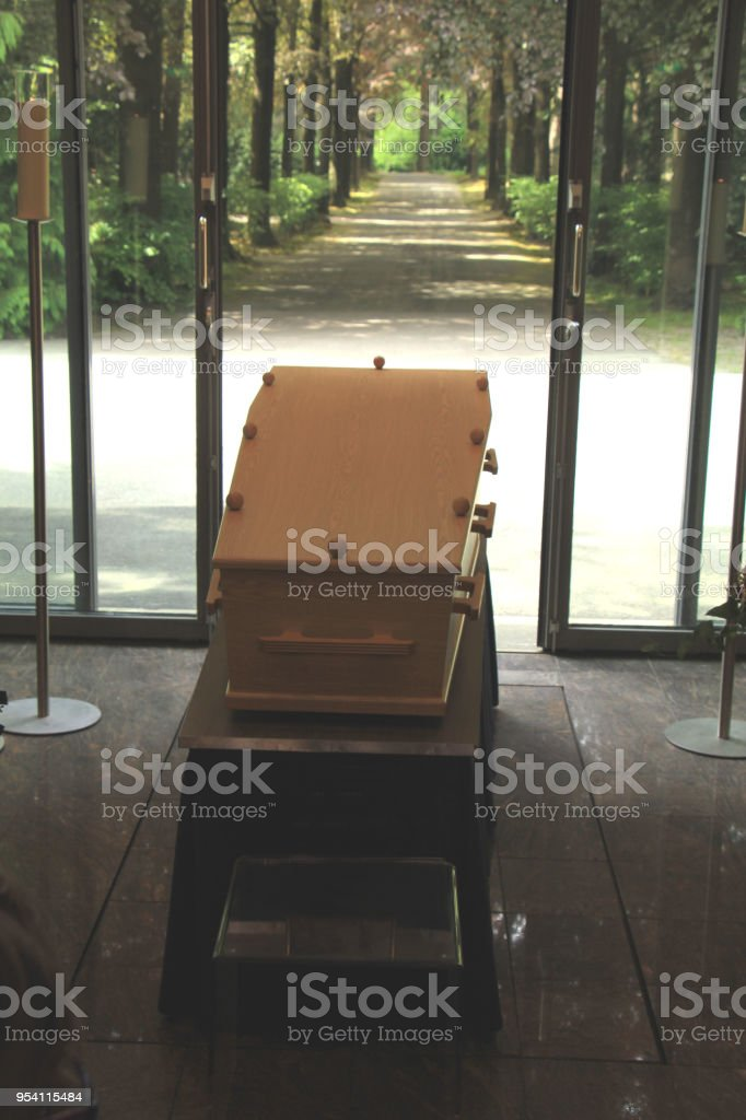 Wooden casket with funeral flowers stock photo