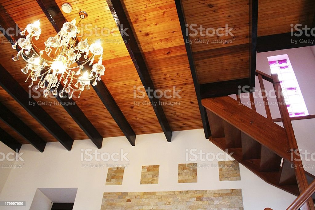 Wooden ceiling, staircase and elegant electrolier royalty-free stock photo