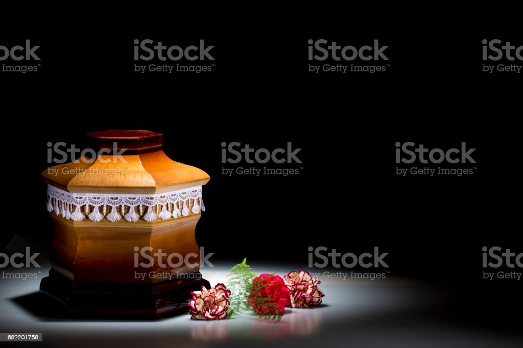 Wooden cemetery urn with blank mourning frame and carnation stock photo