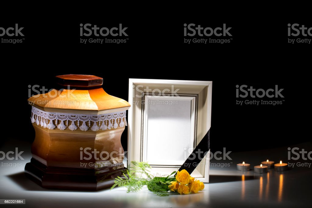 Wooden cemetery urn with blank mourning frame and flower stock photo