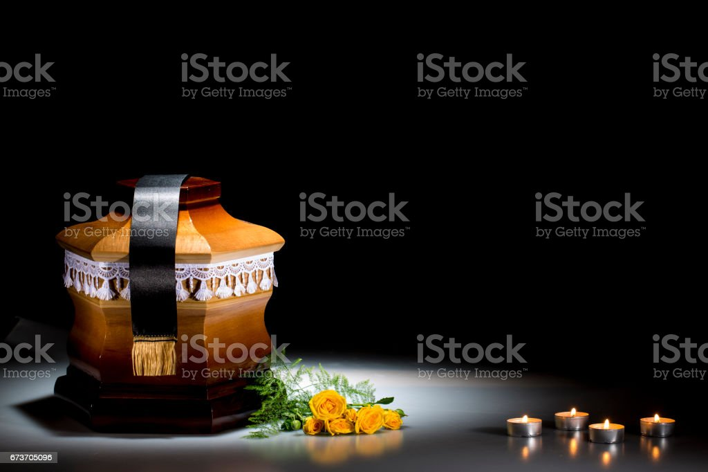 Wooden cemetery urn with yellow roses and candle flames stock photo