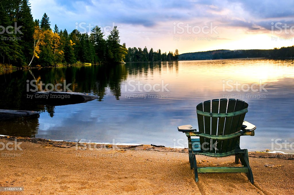 Wooden chair at sunset on beach stock photo