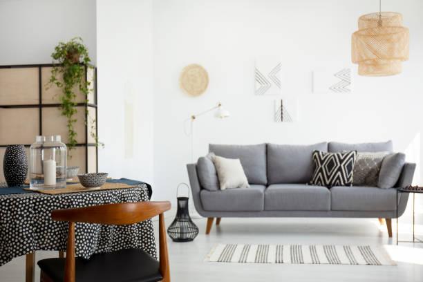 holzstuhl am tisch in weiß wohnzimmer interieur mit lampe und grau sofa mit kissen. echtes foto - traumfänger malerei stock-fotos und bilder