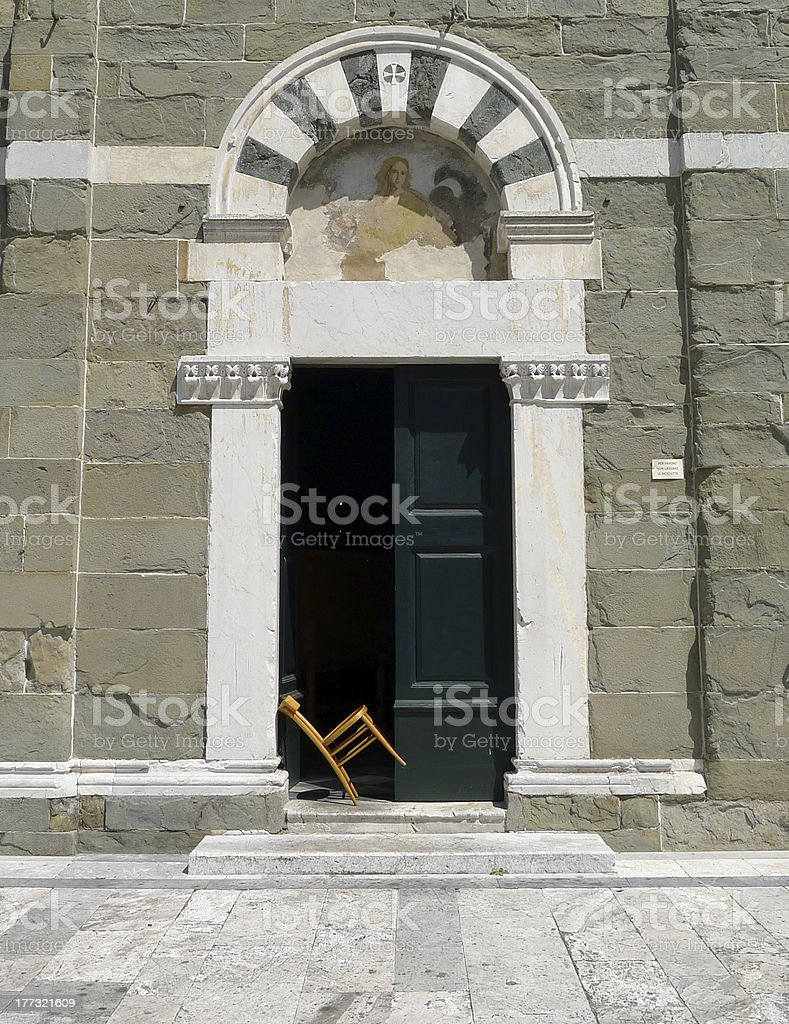 Wooden chair in entrance of  a church, Lucca, Italy royalty-free stock photo