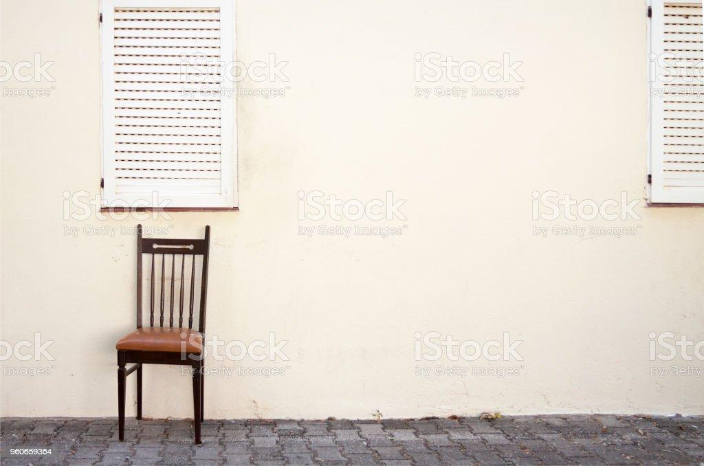 Holzstuhl draußen auf der Straße gegen eine Wand in einem mediterranen Ambiente mit Fensterläden – Foto