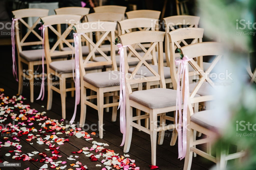 Wooden chairs are decorated with pink bow, ribbons and greens in the backyard banquet area. Wedding ceremony. Roses petals scattered on the road. wedding decor. Side view and front view. stock photo