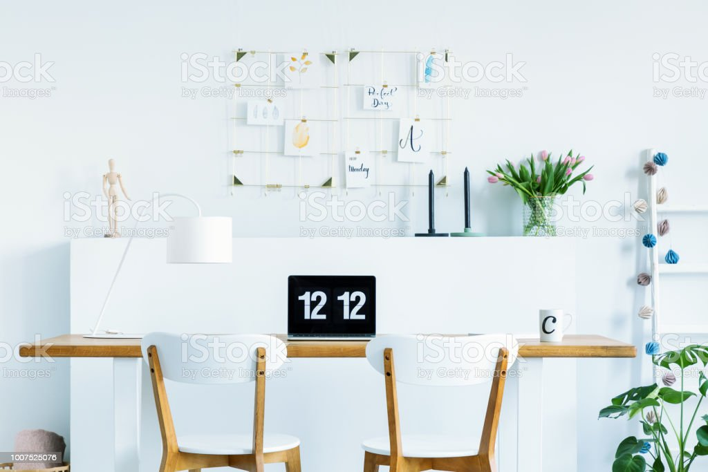 Wooden chairs at desk with laptop and lamp in white home office interior with flowers. Real photo