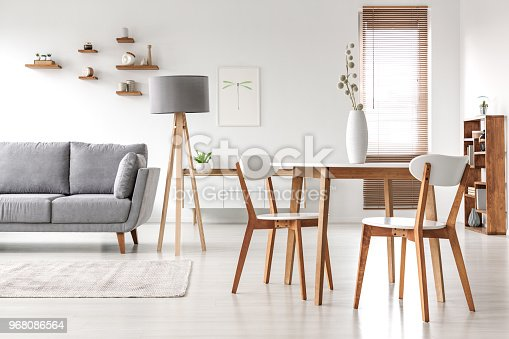 istock Wooden chairs at table in bright open space interior with lamp next to grey couch. Real photo 968086564