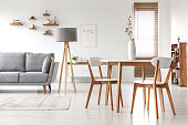 Wooden chairs at table in bright open space interior with lamp next to grey couch. Real photo