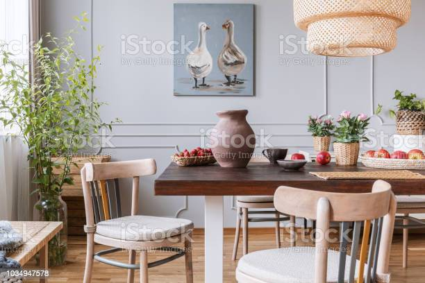 Wooden chairs at table with flowers in natural dining room interior picture id1034947578?b=1&k=6&m=1034947578&s=612x612&h=ufy60mtrjaynjj5qz50zwp zhibt8xumwdrid7kebou=