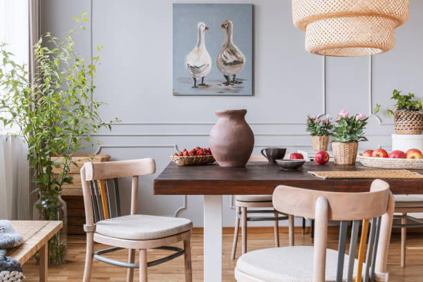 Wooden chairs at table with flowers in natural dining room interior with poster and lamp. Real photo stock photo